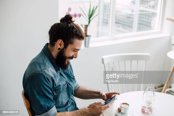 smiling young man typing on his phone at a coffee shop - man bun stock pictures, royalty-free photos & images