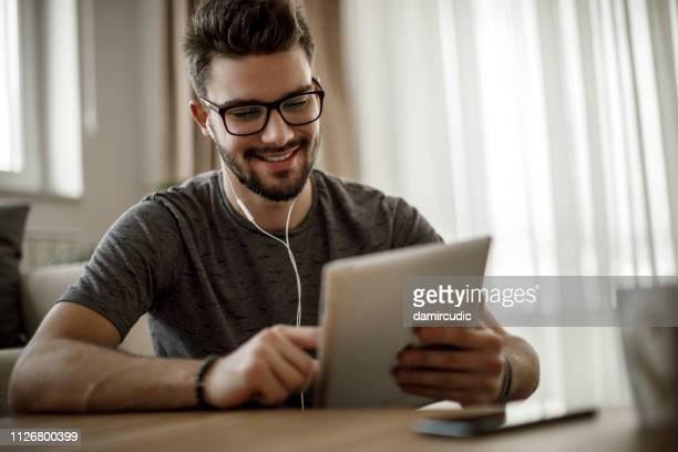 家庭でデジタル タブレットを使用して笑顔の若い男 - insight tv ストックフォトと画像