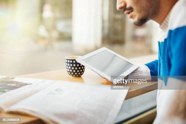 smiling young man using digital tablet in cafe - newspaper stock pictures, royalty-free photos & images