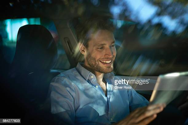 Smiling young man using digital tablet inside car