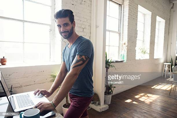 Smiling young man using laptop in a loft