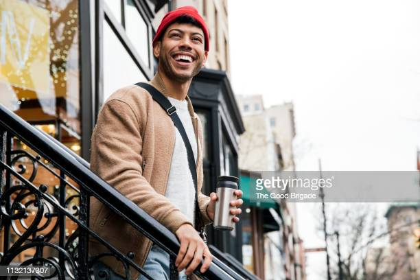 smiling young man walking down stairs in city - red hat stock pictures, royalty-free photos & images