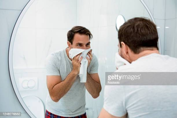 smiling young man washing face in morning in bathroom - shaved stock pictures, royalty-free photos & images