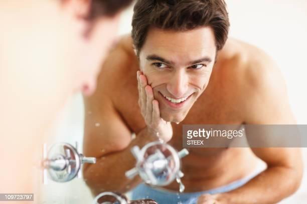 Smiling young man washing his face at the basin