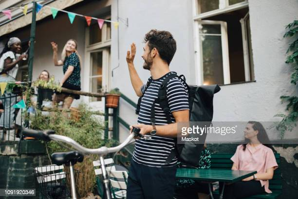 smiling young man waving hand while standing with bicycle in backyard - winken stock-fotos und bilder