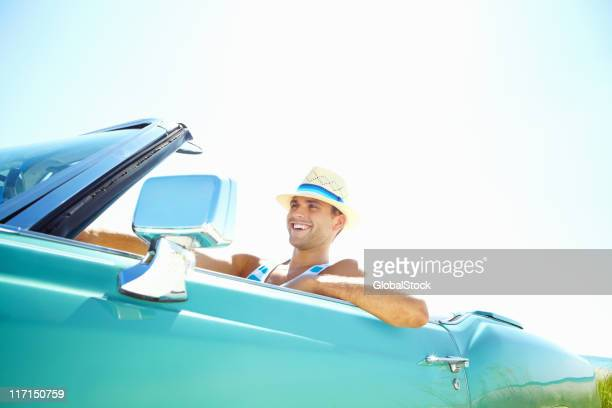 Smiling young man wearing hat while driving convertible car