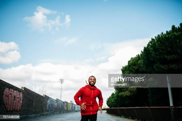 smiling young man wearing red hoodie running in the city - black jacket stock photos and pictures