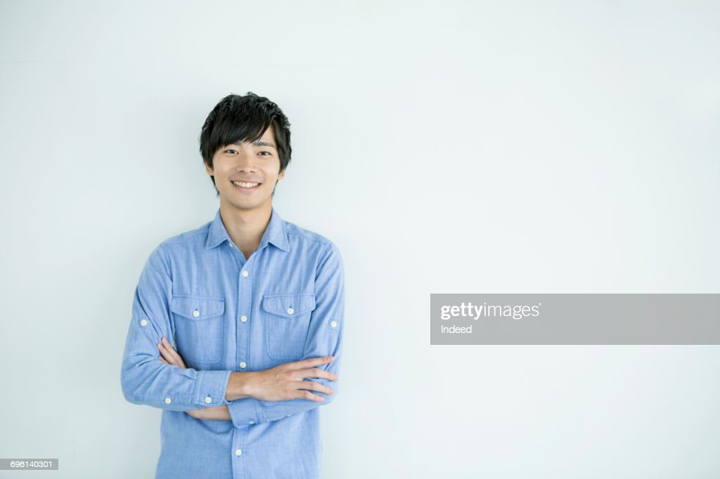 Smiling young man with arms crossed : Stock Photo