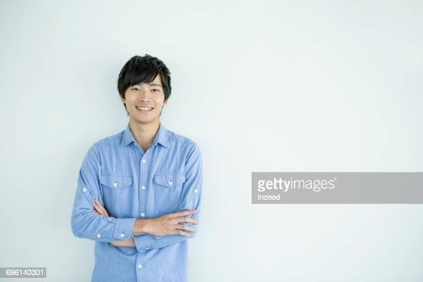 smiling young man with arms crossed - waist up stock pictures, royalty-free photos & images