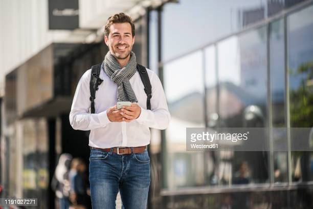 smiling young man with backpack and cell phone in the city on the go - solo un uomo giovane foto e immagini stock