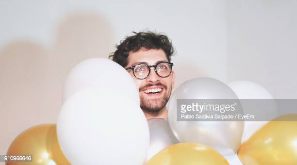 Smiling Young Man With Balloons Against White Background