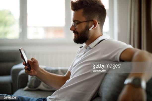 自宅でスマートフォンを使用してブルートゥースヘッドフォンで笑顔の若者 - ブルートゥース ストックフォトと画像