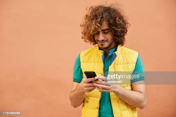 smiling young man with curly hair wearing yellow waistcoat looking at cell phone - waistcoat stock pictures, royalty-free photos & images