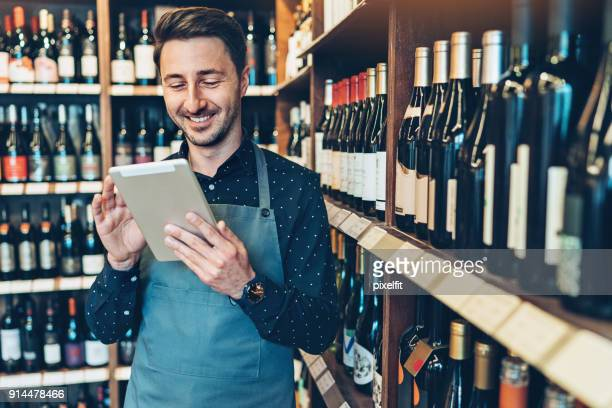 smiling young man with digital tablet in a wine shop - liquor store stock pictures, royalty-free photos & images