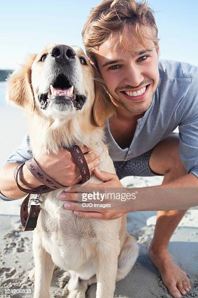 Smiling young man with dog at the beach