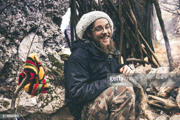 Smiling Young Man with Dreadlocks Sitting By a Fireplace in Nature