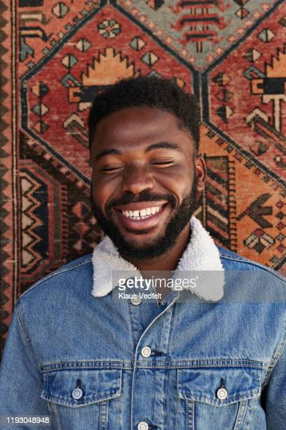 smiling young man with eyes closed against patterned wall - denim jacket stock pictures, royalty-free photos & images