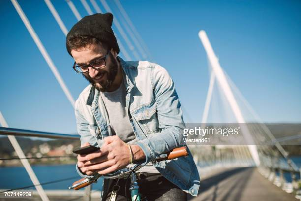 Smiling young man with fixie bike using a smartphone on a bridge