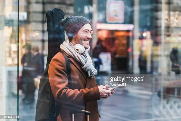 smiling young man with guitar case and cell phone - bahnhof stock-fotos und bilder
