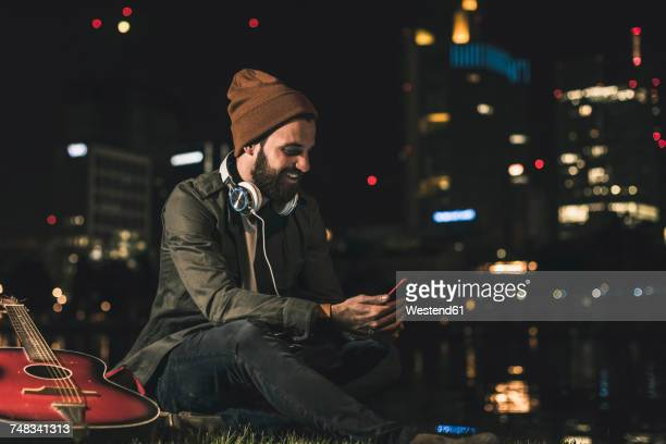 Smiling young man with guitar, cell phone and headphones sitting at urban riverside at night