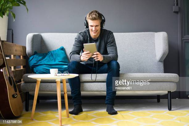 smiling young man with guitar, tablet and headphones sitting on couch - one young man only ストックフォトと画像