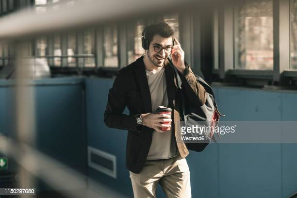 smiling young man with headphones, cell phone and takeaway coffee walking at the station - unterwegs stock-fotos und bilder