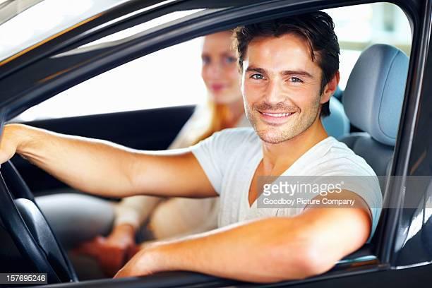 Souriant jeune homme avec sa petite amie dans la nouvelle voiture