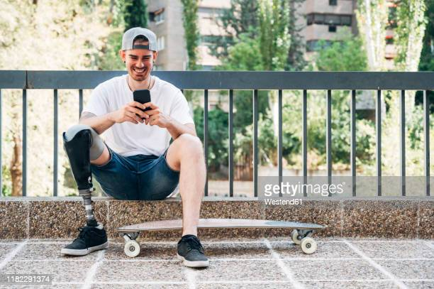smiling young man with leg prosthesis and skateboard using smartphone - persons with disabilities stock pictures, royalty-free photos & images