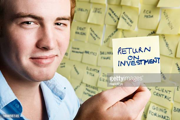 Smiling young man with return on investment note