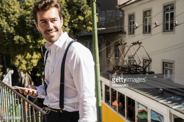smiling young man with smartphone and earbuds in the city, lisbon, portugal - camisa blanca fotografías e imágenes de stock