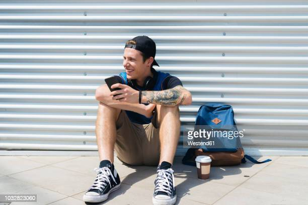 Smiling young man with smartphone, backpack and coffee to go sitting on the ground