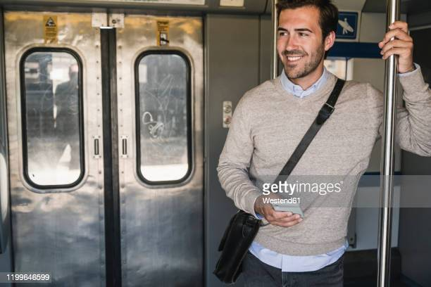 smiling young man with smartphone on a train - bahnreisender stock-fotos und bilder