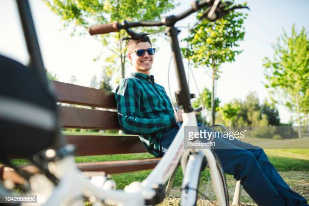 smiling young man with smartphone on park bench - pedalantrieb stock-fotos und bilder
