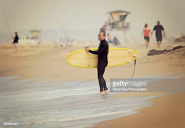 Smiling Young Man with Surfboard