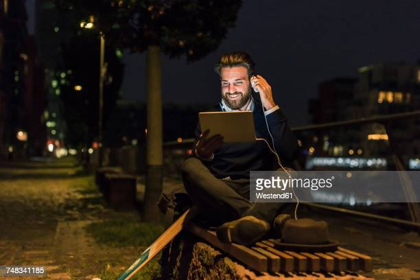 Smiling young man with tablet and headphone in the city at night