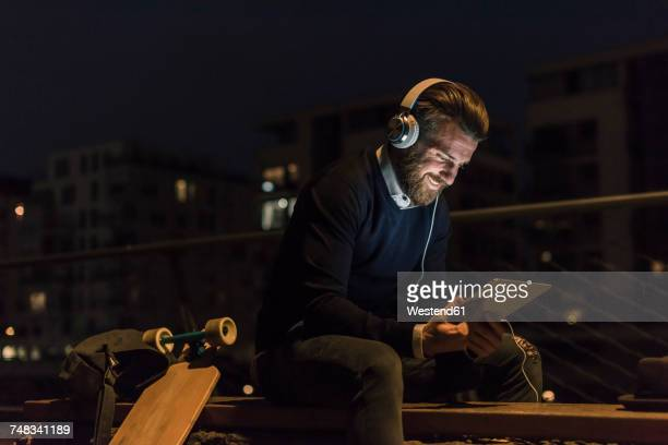Smiling young man with tablet and headphones in the city at night
