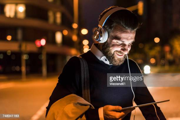 Smiling young man with tablet and headphones on urban street at night