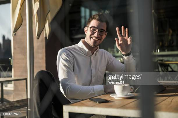smiling young man with tablet at outdoor cafe waving - waving stock pictures, royalty-free photos & images