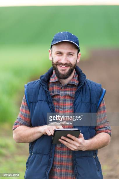 smiling young man with tablet on country road - agronomist stock pictures, royalty-free photos & images