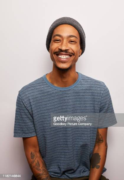 smiling young man with tattoos standing against a gray background - tattoo stock pictures, royalty-free photos & images