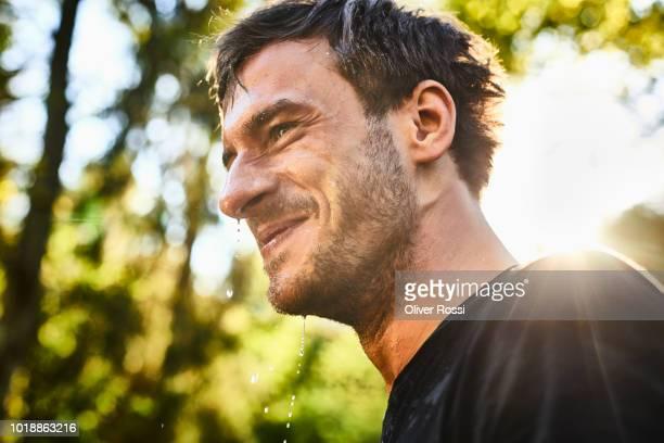 smiling young man with wet face - ungestellt stock-fotos und bilder