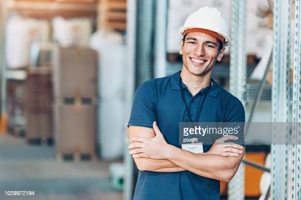 smiling young man with work helmet in a warehouse - polo shirt stock pictures, royalty-free photos & images