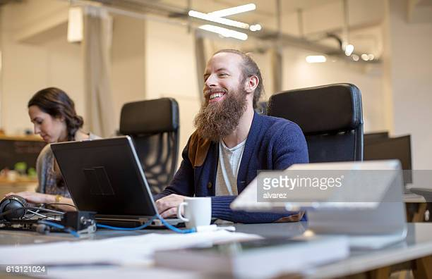 Smiling young man working in modern office