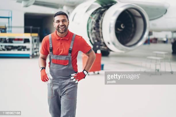 lächelnder junger mann arbeitet im hangar - techniker stock-fotos und bilder