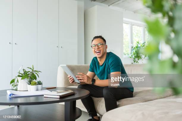 smiling young man working on digital tablet in the office - asian stock pictures, royalty-free photos & images