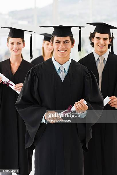 Smiling young men and women holding graduation certificates