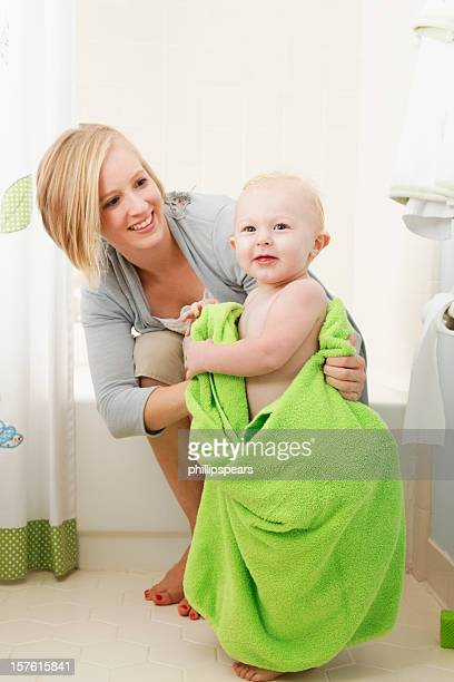 smiling young mother and toddler at bathtime. - mother daughter towel stock photos and pictures