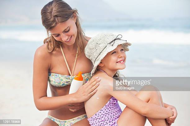 Lächelnde junge Mutter anwenden Körperlotion auf Tochter's back