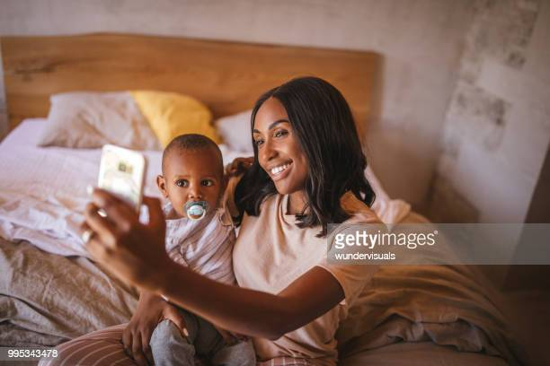 Smiling young mother taking selfies with little son at home