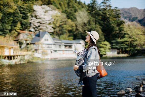 smiling young mother with little daughter sightseeing at lake and enjoying the beautiful scenics and lovely weather - 里山 ストックフォトと画像